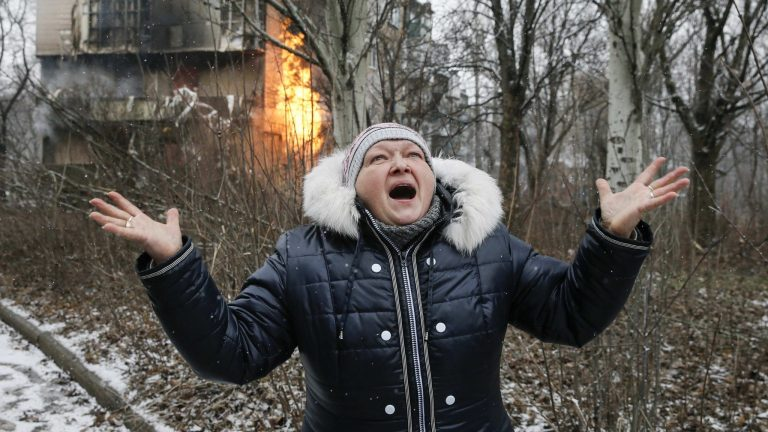A woman reacts as the residential block (back) in which she lives in burns, a result of recent shelling according to locals, on the outskirts of Donetsk, eastern Ukraine February 9, 2015. REUTERS/Maxim Shemetov (UKRAINE  - Tags: POLITICS CIVIL UNREST CONFLICT)