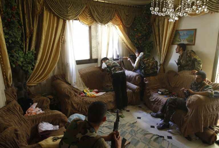 A Free Syrian Army fighter fires his sniper rifle from a house in Aleppo in this August 14, 2012 file photo. Some fighters took position in the living room of a family house. One rebel sits on the chair eating a chocolate bar as the commander looks out the window to scout the area beside a rebel firing from the window. They told me it was a former Syrian army position and they had killed three soldiers in the house - I could see tracks of blood in the corridor -  and taken over their position. There was no one else in the house, except the rebels. REUTERS/Goran Tomasevic/Files (SYRIA - Tags: CIVIL UNREST TPX IMAGES OF THE DAY)  ATTENTION EDITORS - PICTURE 07 16 FOR PACKAGE 'INSIDE SYRIA WITH REBELS' - RTR371GS