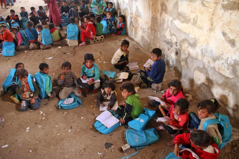 Syrian children sit during class a barn that has been converted into a makeshift school to teach internally displaced children from areas under government control, in a rebel-held area of Daraa, in southern Syria on November 10, 2016. The school has a shortage of seats prompting many children to sit on stones instead. Rebels hold most of Daraa province, but the regional capital is largely controlled by the government.   / AFP PHOTO / MOHAMAD ABAZEED