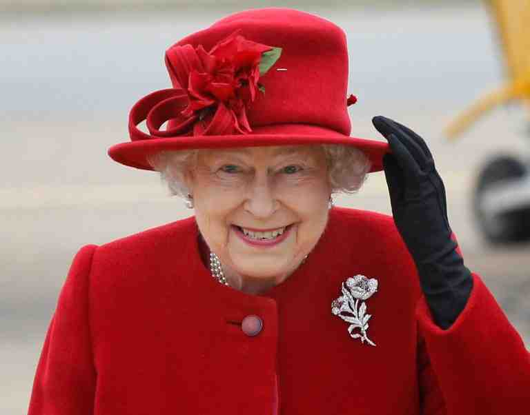 HOLYHEAD, UNITED KINGDOM - APRIL 01:  Queen Elizabeth II holds on to her hat in high winds during a visit to RAF Valley where Prince William is stationed as a search and rescue helicopter pilot on April 1, 2011 in Holyhead, United Kingdom. The Queen toured the airbase meeting staff and families, watched a fly past and was given a guided tour of a Sea King search and rescue helicopter by Prince William.  (Photo by Christopher Furlong-WPA-Pool/Getty Images)