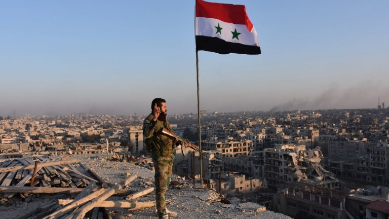 TOPSHOT - Syrian pro-government forces stand on top of a building overlooking Aleppo in the city's Bustan al-Basha neighbourhood on November 28, 2016, during their assault to retake the entire northern city from rebel fighters. In a major breakthrough in the push to retake the whole city, regime forces captured six rebel-held districts of eastern Aleppo over the weekend, including Masaken Hanano, the biggest of those in eastern Aleppo.    / AFP / GEORGE OURFALIAN        (Photo credit should read GEORGE OURFALIAN/AFP/Getty Images)