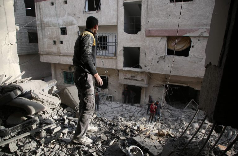 A member of the Syrian civil defence forces known as White Helmets checks the site of an air strike in the rebel-held enclave of Arbin in the Eastern Ghouta near Damascus on February 8, 2018. The death toll from Syrian regime air strike on the rebel-held enclave of Eastern Ghouta near Damascus rose to 36, a monitor said. Ten children and seven women were among today's victims, bringing to 185 the number of civilians killed over the past four days, said Rami Abdel Rahman, head of the Britain-based Observatory / AFP PHOTO / Amer ALMOHIBANY