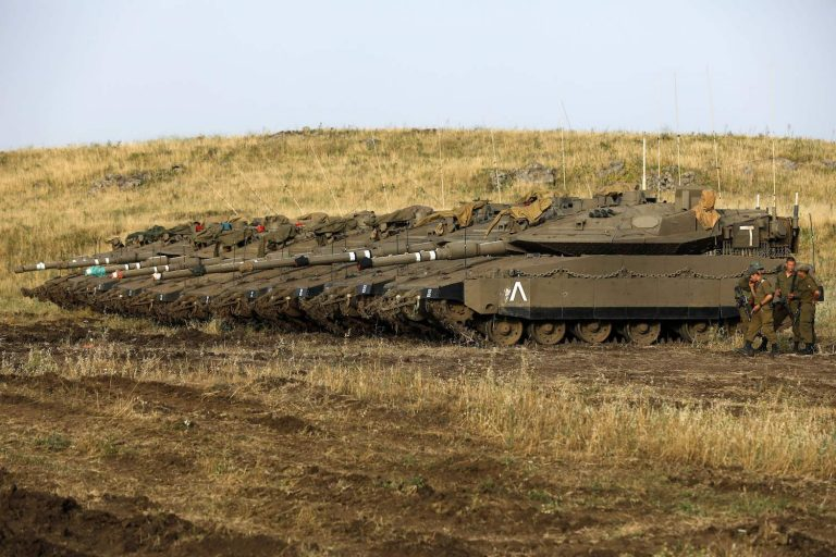 Israeli soldiers stand next to Merkava Mark IV tanks in a deployment area near the Syrian border in the Israel-annexed Golan Heights on May 10, 2018. - Israel's army said today it had carried out widespread raids against Iranian targets in Syria overnight after rocket fire towards its forces it blamed on Iran, marking a sharp escalation between the two enemies. Israel carried out the raids after it said around 20 rockets, either Fajr or Grad type, were fired from Syria at its forces in the occupied Golan Heights at around midnight. (Photo by MENAHEM KAHANA / AFP)        (Photo credit should read MENAHEM KAHANA/AFP/Getty Images)