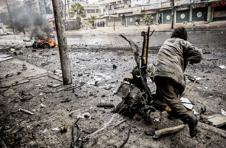 A man removes debris of a truck damaged after a mortar shell hit a street killing several people in the Bustan Al-Qasr district of Aleppo, on December 17, 2012.(AP Photo/Narciso Contreras)