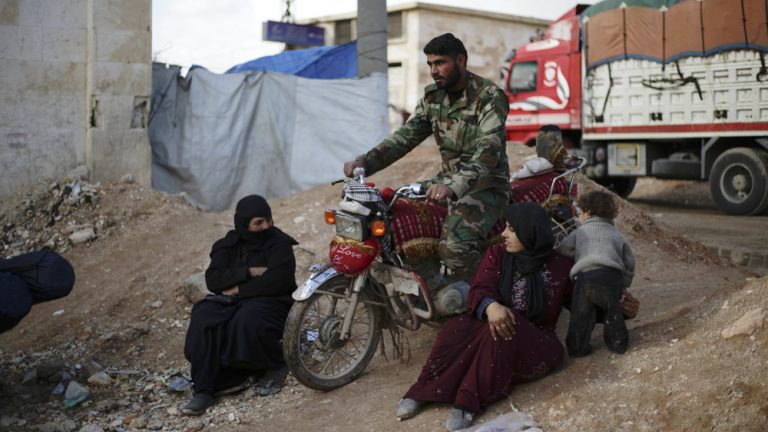 A Syrian soldier passes by Syrian women that displaced with their families from eastern Aleppo in the village of Jibreen south of Aleppo, Syria, Saturday, Dec. 3, 2016. Aid agencies say that more than 30,000 people have fled rebel-held eastern neighborhoods of Aleppo that have been under tight siege since July. Over the past two weeks, government forces launched an offensive in which they regained control of nearly half areas that had been held by insurgents in their deepest push since the city became contested in July 2012.(AP Photo/Hassan Ammar)