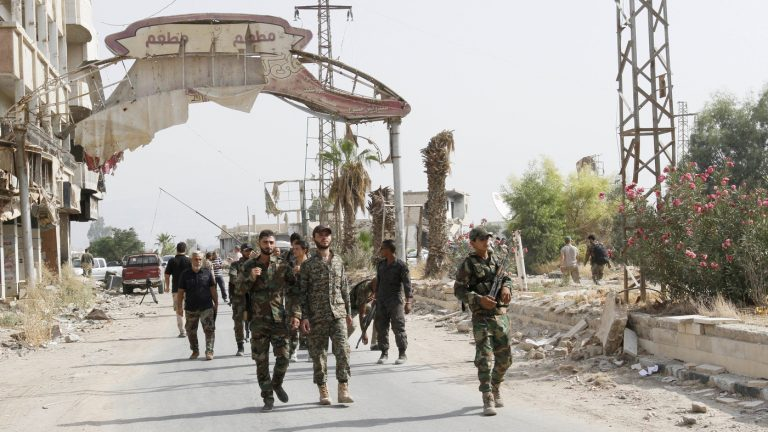 Syrian soldiers walk at the entrance of Daraya, a besiegedDamascus suburb, on Friday