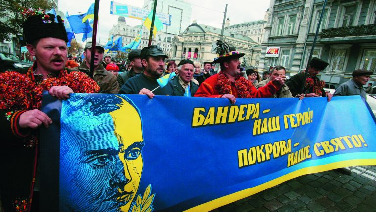 ITAR-TASS 152: KIEV, UKRAINE. OCTOBER 14, 2009. Men in traditional Ukrainian costume carry a banner showing head of OUN's terrorist unit, Stepan Bandera, during a demonstration marking the 67th anniversary of Ukrainian Insurgent Army (UPA) in capital Kiev. The banner reads: