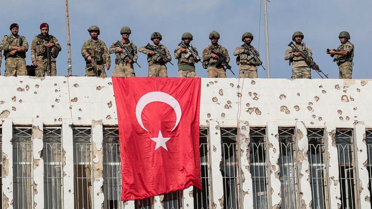 FILE - In this Wednesday, Oct. 23, 2019 file photo, Turkish soldiers, right, and Turkey-backed opposition fighters stand atop a building next to their flags in Ras al Ayn, northeastern Syria. Turkey's army said Sunday, Oct. 27, 2019, that an attack by Kurdish fighters in northeast Syria killed one of its personnel and wounded five others, bringing Turkey's military death toll to 11 since the launch of its operation. The military said the attack occurred near the border town of Ras al-Ayn where its forces were conducting reconnaissance. (Ugur Can/DHA via AP, File)