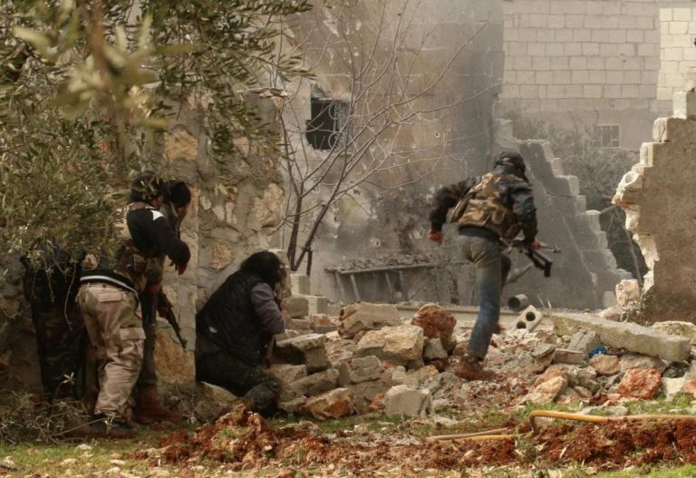 A rebel fighter carries his weapon as he runs while others take positions in Ratian village, north of Aleppo, after what the rebels said was an offensive against them by forces loyal to Syria's President Bashar al-Assad that attempted to advance in the village but failed to February 18, 2015. REUTERS/Ammar Abdullah