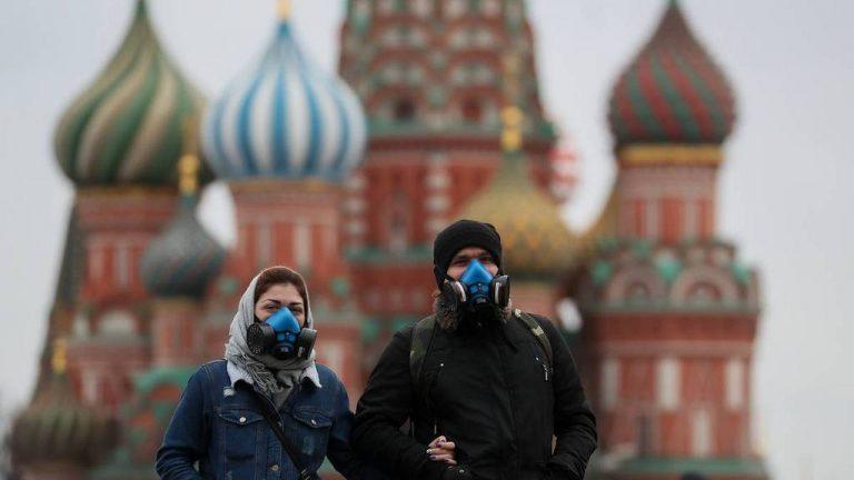 MOSCOW, RUSSIA - MARCH 21, 2020: A young couple in respirators walk in Red Square near St Basil's Cathedral. As of 21 March 2020, Russia has confirmed more than 250 cases of the novel coronavirus, with more than 130 cases in Moscow. Sergei Savostyanov/TASS  Ðîññèÿ. Ìîñêâà. Ìîëîäûå ëþäè â ïðîòèâîãàçîâûõ ìàñêàõ ó Õðàì Âàñèëèÿ Áëàæåííîãî íà Êðàñíîé ïëîùàäè. Ñåðãåé Ñàâîñòüÿíîâ/ÒÀÑÑ