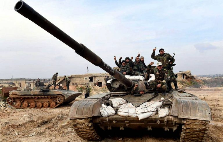 This Monday, Jan. 27, 2020, photo, released by the Syrian official news agency SANA, Syrian army soldiers flash the victory sign as they stand on their tank in western rural Aleppo, Syria. Syrian government forces pressed in their offensive Tuesday, Jan. 28, 2020, closing in on a major rebel stronghold in the northwestern province of Idlib and marching against insurgents west of Aleppo, Syria's largest city, state media and opposition activists said Tuesday. (SANA via AP)