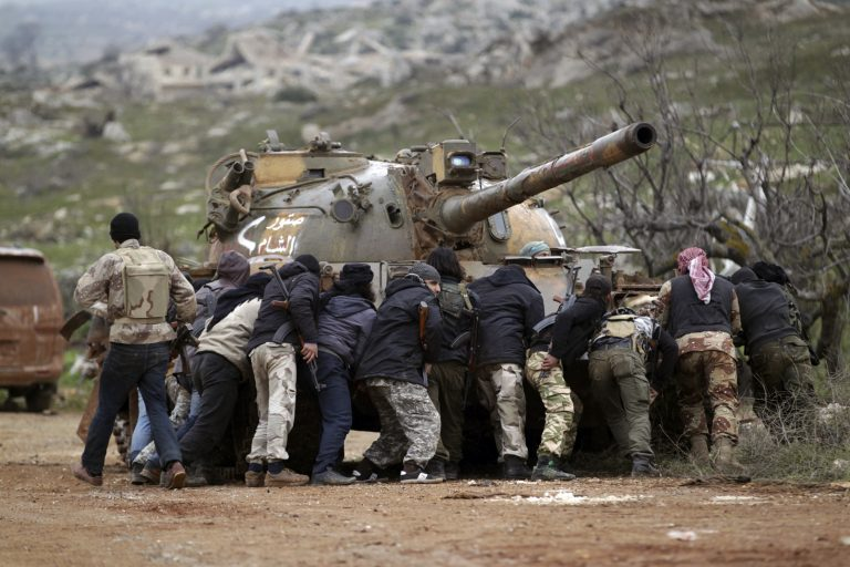 Fighters from the Suqour al-Sham Brigade, which is part of the Free Syrian Army, take cover from snipers behind a tank during what activists said were clashes with forces of Syria's President Bashar al-Assad, in the al-Arbaeen mountain area of western Idlib January 30, 2015. REUTERS/Khalil Ashawi  (SYRIA - Tags: POLITICS CIVIL UNREST CONFLICT TPX IMAGES OF THE DAY) - RTR4NNRX