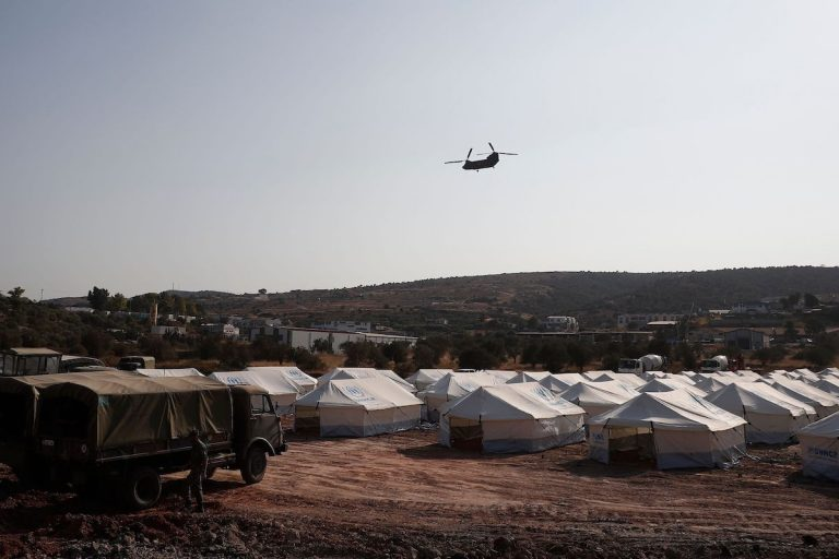 A Greek army's helicopter carrying European Council President flies over the new refugee and migrant camp near Kara Tepe, on the Greek island of Lesbos, days after Europe's largest Moria camp on the island burnt down on September 15, 2020. - The German government confirmed on September 15, 2020, that it has agreed to take in 1,553 refugees from Greece, on top of the 150 unaccompanied minors it will offer refuge to after their camp burned down on the island of Lesbos. (Photo by DIMITRIS TOSIDIS / POOL / AFP) (Photo by DIMITRIS TOSIDIS/POOL/AFP via Getty Images)