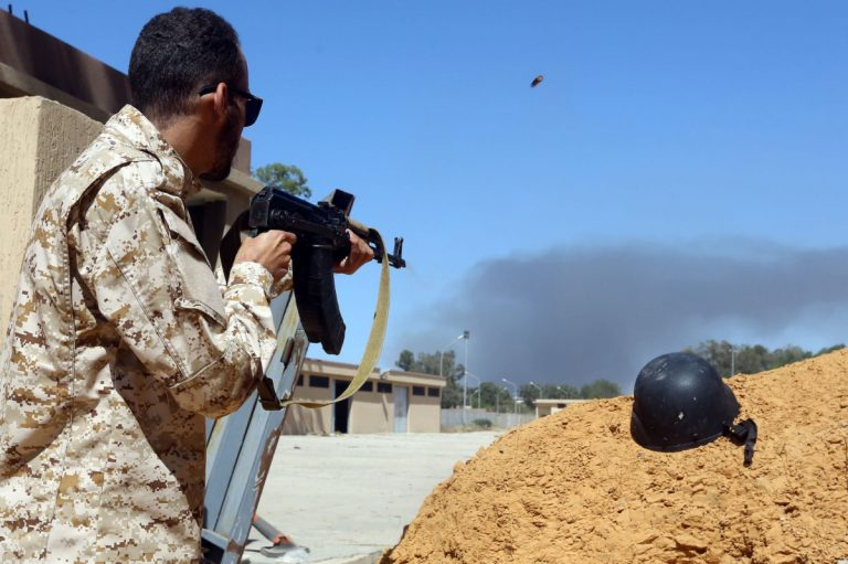 A fighter loyal to the internationally recognised Libyan Government of National Accord (GNA) keeps position near the Salah al-Din military compound, south of the Libyan capital Tripoli, on May 7, 2019. - Troops loyal to military strongman Khalifa Haftar said today they shot down a warplane of rival forces of Libya's unity government near Tripoli and captured its foreign
