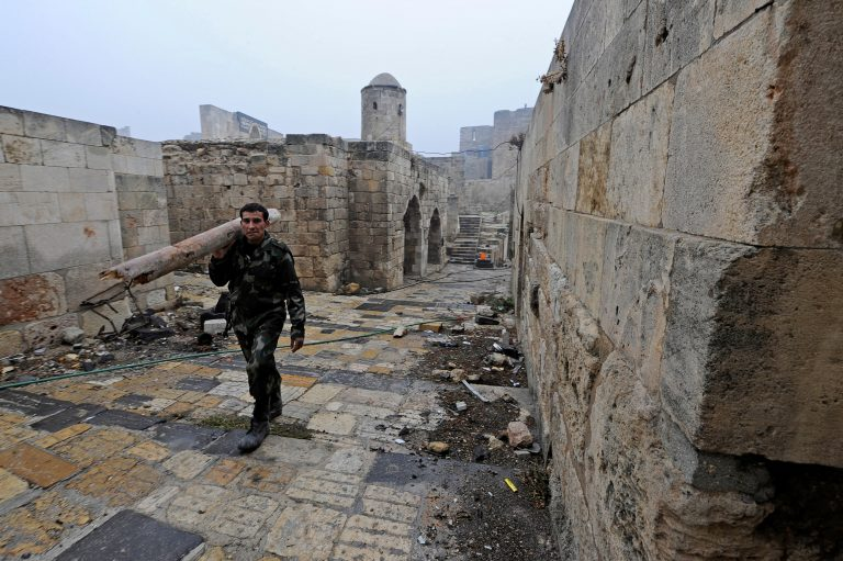 A member of forces loyal to Syria's President Bashar al-Assad carries a tree branch as he walks inside Aleppo's historic citadel, during a media tour, Syria December 13, 2016. REUTERS/Omar Sanadiki